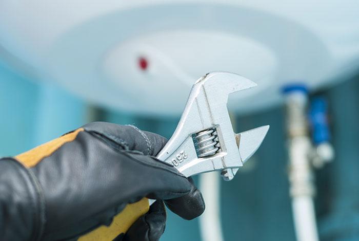 Plombier intervenant sur un ballon d'eau chaude