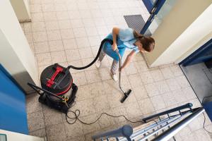 Femme de ménage passant l'aspirateur dans un hall d'immeuble